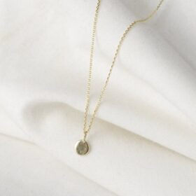 Beautiful hypoallergenic gold dot necklace laid flat on a white cloth.