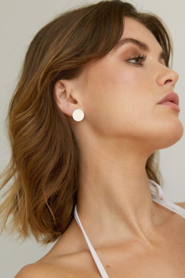 Woman wearing an ethically-made sterling silver contemporary silver disc studs.