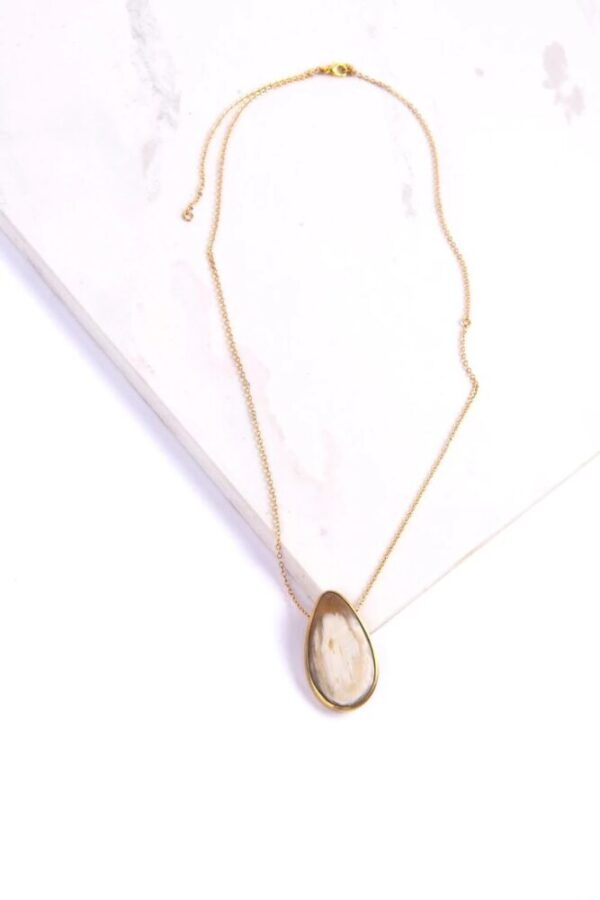 Beautifully upcycled white horn and brass on a gold-colored brass chain Maystone necklace on a white background.
