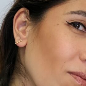 Woman showcasing her ethically-made minimalist Gold Classic Bar studs.