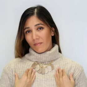 Woman fashionably wears Ethically made Stone treasure necklace on a knitted turtleneck top.