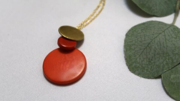 Environmentally friendly Overlapping Round Brass and Red Tagua Disc Pendant and adjustable brass chain.