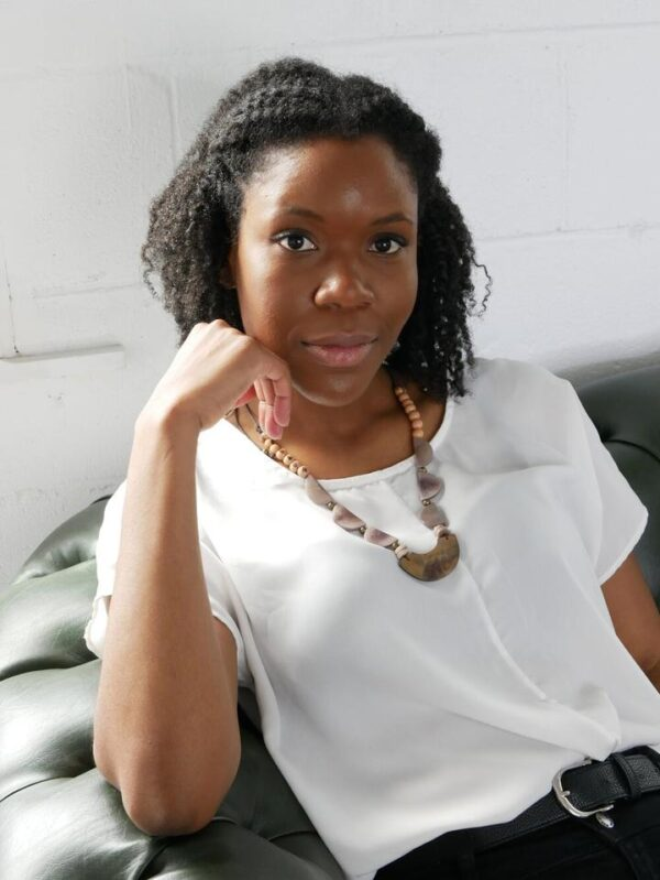 Woman confidently wears the Wildness Necklace that beautifully sits over her white blouse.