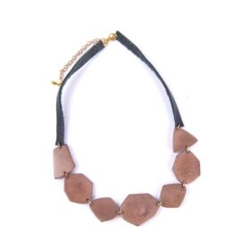 ethically made wonder necklace made of tagua seeds connected by lobster clasp, leather and cold colored extender chair.